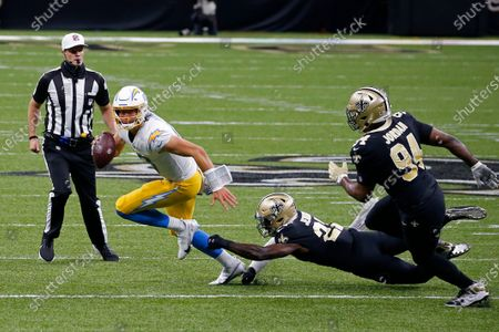 Los Angeles Chargers quarterback Justin Herbert scrambles under pressure from Los Angeles Chargers running back Joshua Kelley and defensive end Cameron Jordan (94) in the first half of an NFL football game in New Orleans