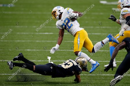 Los Angeles Chargers running back Justin Jackson (22) is tripped up by New Orleans Saints cornerback Marshon Lattimore (23) in the first half of an NFL football game in New Orleans