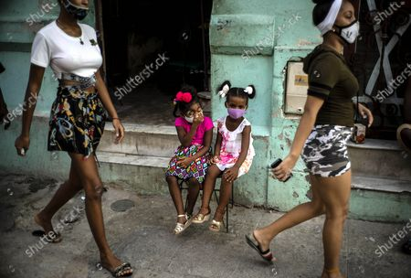 Stock Image of Wearing a mask as a precaution against the spread of the new coronavirus Angelica Victoria, center left, and Thalia Oneida, wait for their parents sitting on a chair in Havana, Cuba, . Cuba relaxed coronavirus restrictions Monday in hopes of boosting its economy, allowing shops and government offices to reopen and welcoming locals and tourists at airports across the island except in Havana