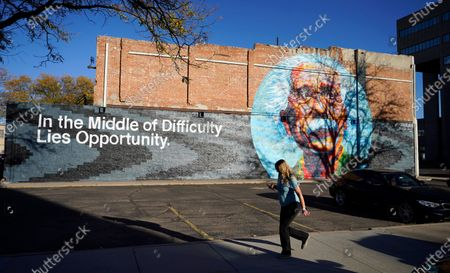 Pedestrian moves past a mural of Albert Einstein on the side of a bicycle shop, in Greeley, Colo