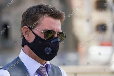 Actor Tom Cruise wears a face mask to prevent the spread of COVID-19 as he greets fans during a break from shooting Mission Impossible 7, along Rome's Fori Imperiali avenue
