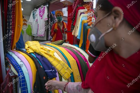 Stock Picture of Woman wearing face mask as a precautionary measure against the coronavirus checks items on display at a clothes store as a holy man waits for alms at its entrance in Kathmandu, Nepal
