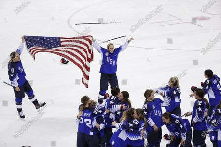 Meghan Duggan (10), of the United States, and Monique Lamoureux-Morando (7), also of the United States, celebrate with teammates after defeating Canada in the women's gold medal hockey game at the Winter Olympics in Gangneung, South Korea. U.S. women's hockey captain Duggan announced her retirement, after a career in which she won the 2018 Olympic gold medal and seven world championship golds