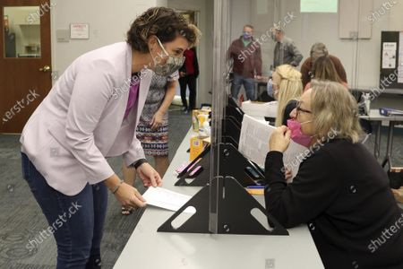 Senate candidate Amy McGrath, left, checks in before voting at the Scott County Public Library in Georgetown, Ky