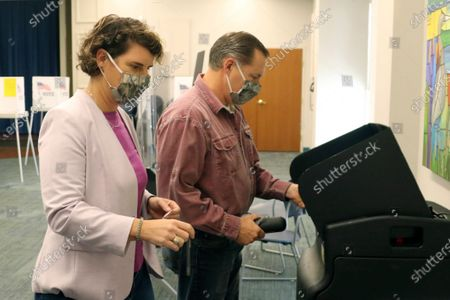 Senate candidate Amy McGrath, left, waits as her husband Erik Henderson scans his voting ballot at the Scott County Public Library in Georgetown, Ky