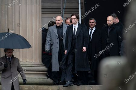"Robert Pattinson, center, is seen on the set of the movie ""The Batman"" at St. George's Hall in Liverpool's city center, England, . The production had a break in filming after the star of the movie Robert Pattinson reportedly testing positive for the virus last month"