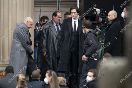 "Colin Farrell, center left, who plays the Penguin, is seen alongside star Robert Pattinson, center, during filming of ""The Batman"" at St. George's Hall in Liverpool's city center, England, . The production had a break in filming after the star of the movie Robert Pattinson reportedly testing positive for the virus last month"