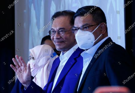 Malaysian opposition leader Anwar Ibrahim waves to the media during a press conference after meeting the nation's king in Kuala Lumpur. Anwar met the king in a bid to form a new government after claiming he had secured a majority in Parliament.