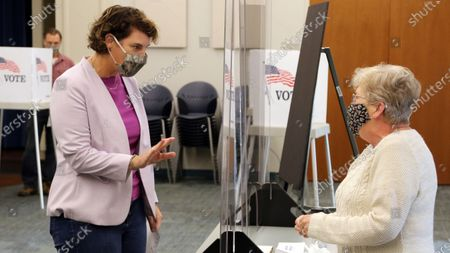 Senate candidate Amy McGrath, left, greets a poll worker after voting at the Scott County Public Library in Georgetown, Ky