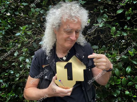 Stock Image of Queen's Brian May with his Official Number 1 Album Award from the Official Charts Company for Live Around The World.