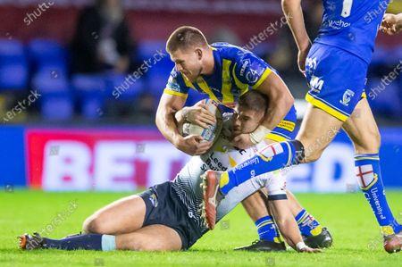 Leeds's Jack Walker is tackled by Warrington's Danny Walker.