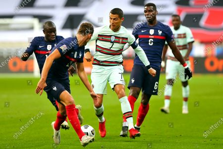 Portugal's Cristiano Ronaldo, center, runs with the ball at France's Benjamin Pavard, foreground, between Ngolo Kante and Paul Pogba, right, during the UEFA Nations League soccer match between France and Portugal at the Stade de France in Saint-Denis, north of Paris, France. The Portuguese soccer federation says Cristiano Ronaldo has tested positive for the coronavirus. The federation says Ronaldo is doing well and has no symptoms. He has been dropped from the country's Nations League match against Sweden on Wednesday, Oct. 14