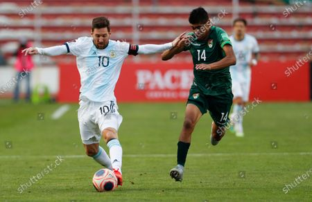 Bolivia's Raul Castro, right, and Argentina's Lionel Messi battle for the ball during a qualifying soccer match for the FIFA World Cup Qatar 2022 in La Paz, Bolivia