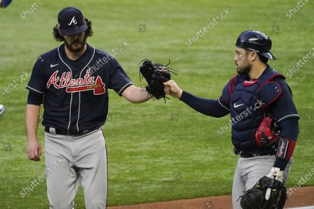 Atlanta Braves starting pitcher Ian Anderson and catcher Travis d'Arnaud celebrate the end of the fourth inning in Game 2 of a baseball National League Championship Series against the Los Angeles Dodgers, in Arlington, Texas