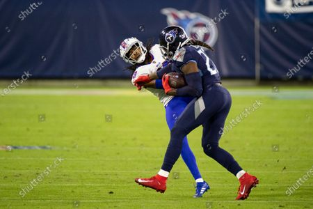 Tennessee Titans running back Derrick Henry (22) stiff arms Buffalo Bills cornerback Josh Norman (29) during the second quarter of an NFL football game, in Nashville, Tenn