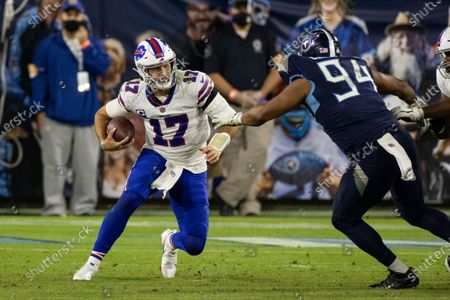 Buffalo Bills quarterback Josh Allen (17) runs with the ball against Tennessee Titans defensive end Jack Crawford (94) during the second half of an NFL football game, in Nashville, Tenn
