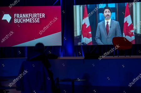 Canadian Prime Minister Justin Trudeau appears on a screen as he delivers a video message at the opening of the 2020 Frankfurt Book Fair amid the coronavirus pandemic in Frankfurt am Main, Germany, 13 October 2020. The Frankfurt Book Fair is the world's largest trade fair for books and is taking place this year at a smaller scale and with many events either online or scattered throughout the city of Frankfurt due to the pandemic. Canada is this year's guest country.