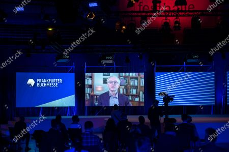 Israeli writer David Grossman appears on a screen as he delivers a video message at the opening of the 2020 Frankfurt Book Fair amid the coronavirus pandemic in Frankfurt am Main, Germany, 13 October 2020. The Frankfurt Book Fair is the world's largest trade fair for books and is taking place this year at a smaller scale and with many events either online or scattered throughout the city of Frankfurt due to the pandemic. Canada is this year's guest country.