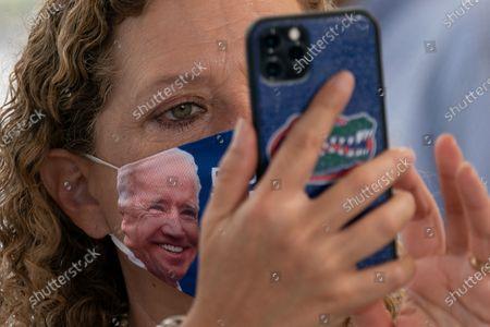 "Wearing a ""Ridin With Biden President 2020"" face mask, Rep. Debbie Wasserman Schultz, D-Fla., looks to her smart phone as Democratic presidential candidate former Vice President Joe Biden speaks at Miramar Regional Park in Miramar, Fla"