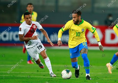 Brazil's Neymar, right, and Peru's Yoshimar Yotun run for the ball during a qualifying soccer match for the FIFA World Cup Qatar 2022 at the National Stadium, in Lima, Peru, Tuesday, Oct.13, 2020