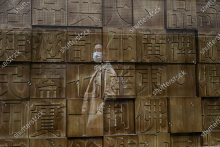 Stock Image of Woman wearing a face mask to help curb the spread of the coronavirus is reflected on a window panel as she walks by a retailed shop displaying Chinese calligraphy fonts in Beijing