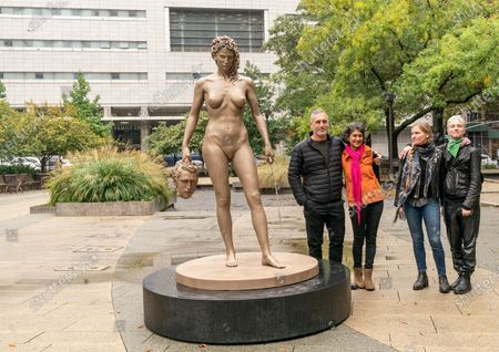Artist Luciano Garbati, Vanessa Solomon, Leah Solomon, Camille Altay stand next to Medusa With The Head of Perseus (MWTH) sculpture unveiled in Collect Pond Park in honor the 'Me Too' movement. Sculpture inverts the narrative of myth of Medusa, portraying her in a moment of somberly empowered self-defense. In myth Medusa is herself blamed and punished for the crime of which she was the victim. Godess Athena banishes and curses Medusa with a monstrous head of snakes and a gaze which turns men to stone. She was beheaded by the epic hero Perseus. Sculpture has been installed directly in front of New York Criminal Court where Harvey Weinstein trial took place.