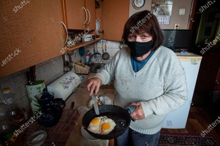 Pensioner Inna while wearing a facemask makes eggs in the kitchen of her apartment during the self-isolation regime recommended by government. Due coronavirus crisis in many regions of the Russia, the government recommended that people over 65 years of age observe a self-isolation regime.
