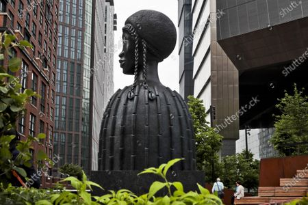 """A bronze bust of a Black woman entitled """"Brick House,"""" by Chicago artist Simone Leigh, stands among buildings and vegetation in the High Line park in New York. Leigh will be the first Black woman ever to represent the U.S. at Italy's prestigious Venice Biennale arts festival to be held in 2022"""