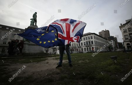 Stock Image of Pro-EU supporter Peter Cook unfurls a Union and EU flag prior to a ceremony to celebrate British and EU friendship outside the European Parliament in Brussels. On the eve of a European Union summit which British Prime Minister Boris Johnson had set as a deadline to get a trade agreement between both sides, talks remained in a deep rut over fundamental differences regarding anything from state aid to fisheries. To push negotiators toward that slim area of possible common ground, EU Commission President Ursula von der Leyen will have a video call with Johnson later Wednesday, Oct. 14, 2020