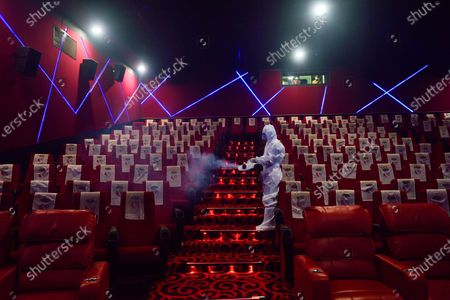 A worker wearing a personal protective equipment suit (PPE) is seen spraying a disinfectant inside a cinema hall in Kolkata following Government's permission to reopen the halls starting 15 Oct with strict Covid-19 safety protocol and proper Standard operating Procedure.