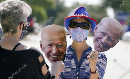 Phyllis Smith, rights, hands her friend Sabina Geiser a Joe Biden face before a Ridin' With Biden event, in Plano, Texas