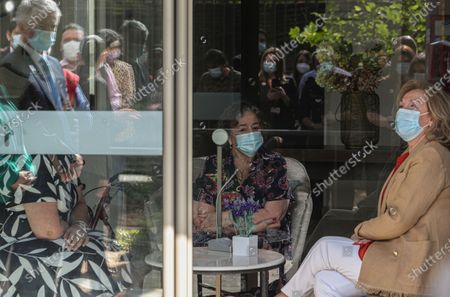 Stock Photo of Chilean First Lady Cecilia Morel meets with Edda Arata, 82, who visits with her relatives from behind a window where she lives at a home for seniors on the day it reopened to visitors amid the COVID-19 pandemic in Santiago, Chile