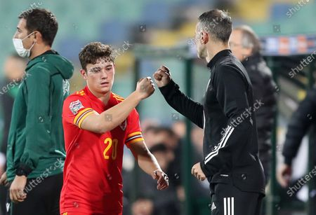 Daniel James of Wales bump fists with Manager Ryan Giggs as he comes off the field.