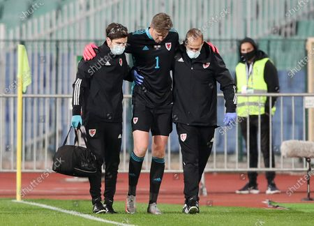 Wayne Hennessey of Wales comes off the field field injured with help from FAW staff.