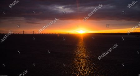 The sun sets behind The Prince of Wales Bridge, formerly Second Severn Crossing, between England and Wales on the day that the Welsh Government announced it would impose restrictions on travel into Wales from areas of high incident rates of COVID-19 in England