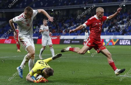 Igor Smolnikov (R) of Russia in action against Hungarian players Attila Szalai (L) and goalkeeper Denes Dibusz (bottom) during the UEFA Nations League soccer match between Russia and Hungary in Moscow, Russia, 14 October 2020.