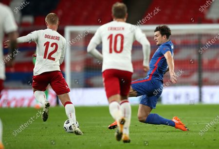 England's Harry Maguire, right, move sin to tackle Denmark's Kasper Dolberg, left, during the UEFA Nations League soccer match between England and Denmark at Wembley Stadium in London, England
