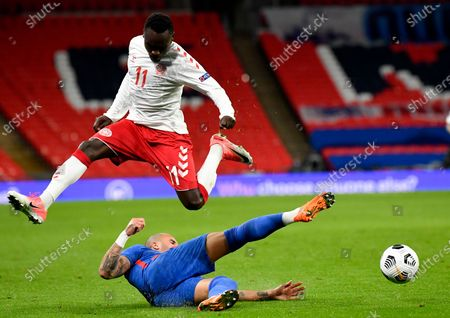 Denmark's Pione Sisto leaps above England's Kyle Walker during the UEFA Nations League soccer match between England and Denmark at Wembley Stadium in London, England
