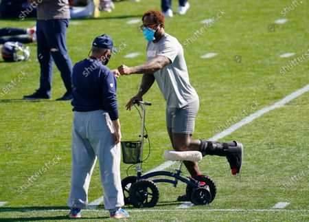 Stock Picture of Injured Denver Broncos outside linebacker Von Miller, right, uses a scooter to maneuver around the practice field as he greets head coach Vic Fangio during an NFL football practice, at the team's headquarters in Englewood, Colo