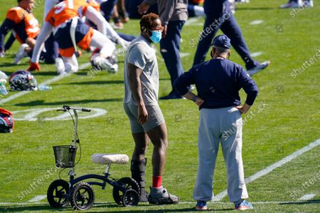 Injured Denver Broncos outside linebacker Von Miller, left, chats with head coach Vic Fangio as players stretch before taking part in drills during an NFL football practice, at the team's headquarters in Englewood, Colo