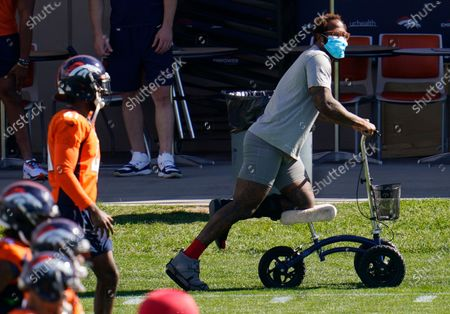 Injured Denver Broncos outside linebacker Von Miller uses a scooter to maneuver around as his teammates warm up before taking part in drills during an NFL football practice, at the team's headquarters in Englewood, Colo