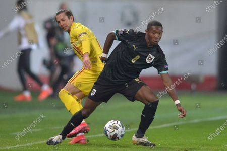 Austria's David Alaba, right, challenges for the ball with Romania's Ciprian Deac during the UEFA Nations League soccer match between Romania and Austria at the Ilie Oana stadium in Ploiesti, Romania
