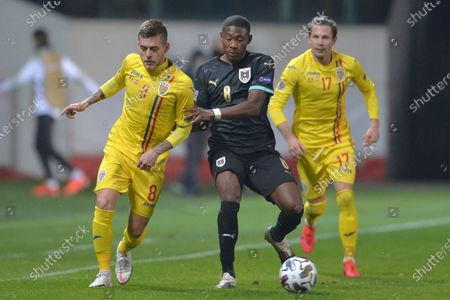 Austria's David Alaba, right, challenges for the ball with Romania's Alexandru Cicaldau during the UEFA Nations League soccer match between Romania and Austria at the Ilie Oana stadium in Ploiesti, Romania