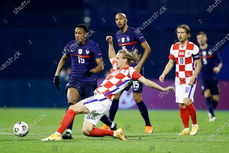 Croatia's Domagoj Vida, front, duels for the ball with France's Anthony Martial, left, during the UEFA Nations League soccer match between Croatia and France at Maksimir Stadium in Zagreb, Croatia