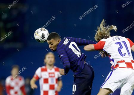 Stock Image of France's Kylian Mbappe, centre, jumps for the ball with Croatia's Domagoj Vida during the UEFA Nations League soccer match between Croatia and France at Maksimir Stadium in Zagreb, Croatia