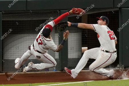 Stock Photo of Atlanta Braves third baseman Johan Camargo catches a fly ball hit by Los Angeles Dodgers' Joc Pederson as third baseman Austin Riley looks on during the third inning in Game 3 of a baseball National League Championship Series, in Arlington, Texas