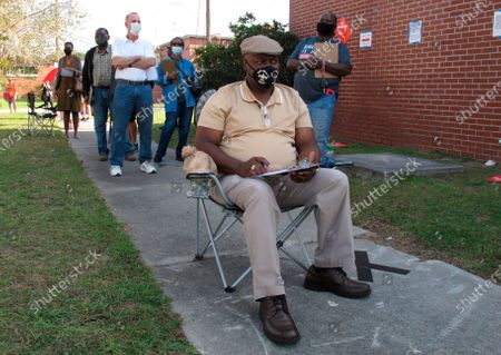 Richard Williams sits in a folding chair, filling out paperwork, as he waits in line to vote early in Savannah, Ga., on . Black people are going to the polls by the thousands and waiting in lines for hours to vote early in Georgia