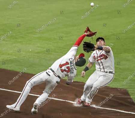 Atlanta Braves third baseman Johan Camargo (L) catches a foul ball hit by Los Angeles Dodgers right fielder Joc Pederson as he nearly collides with Atlanta Braves left fielder Austin Riley (R) in the sixth inning of the National League Championship Series game three between the Los Angeles Dodgers and the Atlanta Braves at Globe Life Field in Arlington, Texas, USA, 14 October 2020.
