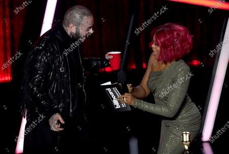 Post Malone, left, accepts the top artist award from Taraji P. Henson at the Billboard Music Awards, at the Dolby Theatre in Los Angeles