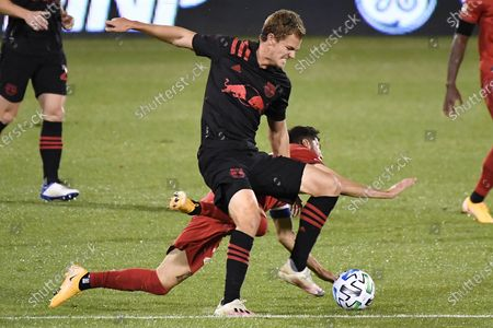 Stock Image of Toronto FC's Jonathan Osorio, bottom, falls as New York Red Bulls' Tom Barlow takes control of the ball during the first half of an MLS soccer match, in East Hartford, Conn